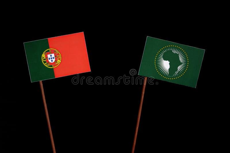 Bandeira portuguesa com a bandeira de união africana no preto fotografia de stock