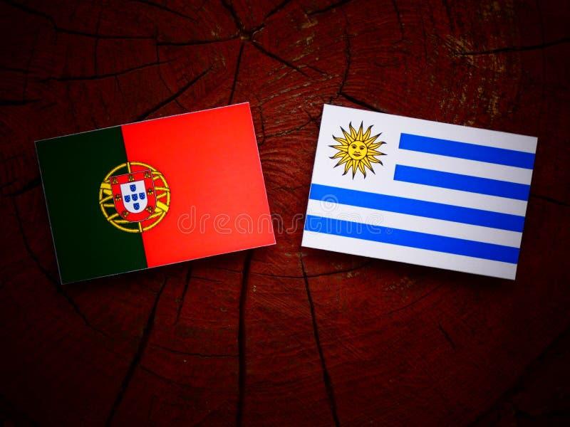 Bandeira portuguesa com bandeira de Uruguaian em um coto de árvore isolado foto de stock royalty free