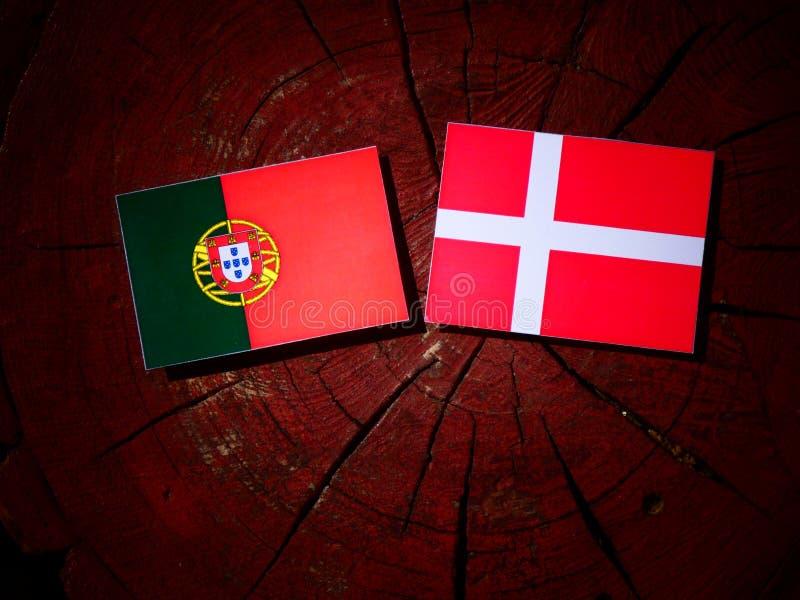 Bandeira portuguesa com bandeira dinamarquesa em um coto de árvore isolado fotos de stock