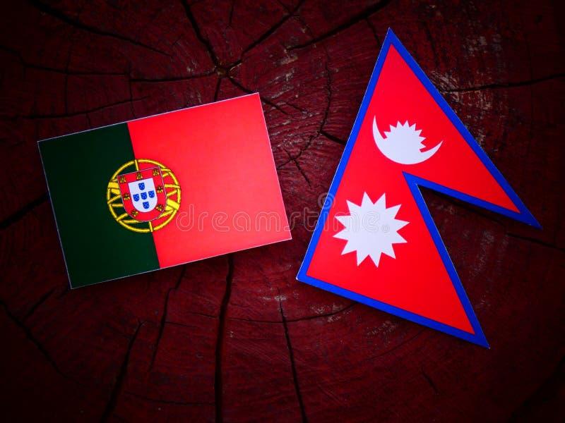 Bandeira portuguesa com bandeira do Nepali em um coto de árvore isolado imagem de stock
