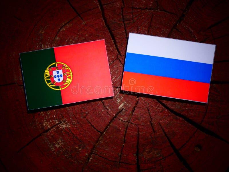 Bandeira portuguesa com bandeira do russo em um coto de árvore fotografia de stock