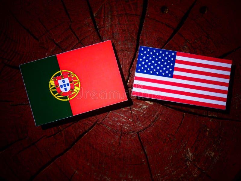 Bandeira portuguesa com bandeira dos EUA em um coto de árvore imagens de stock royalty free