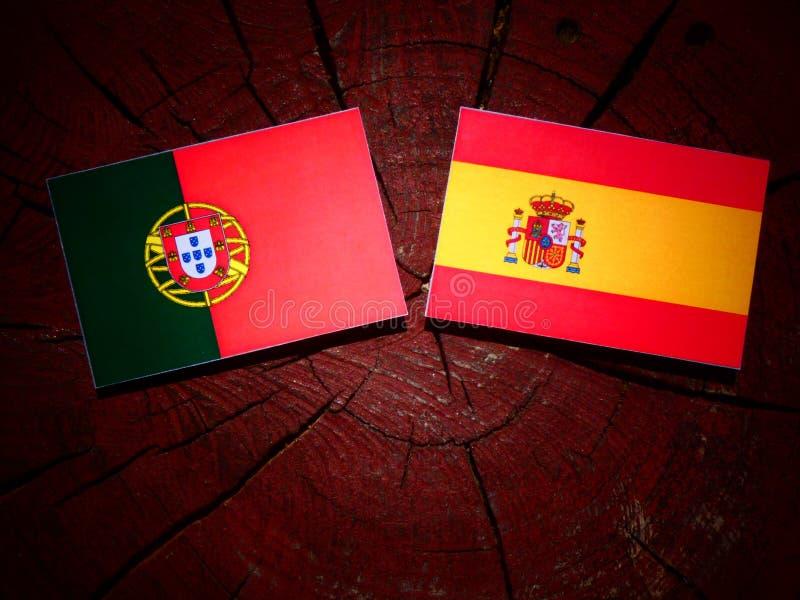 Bandeira portuguesa com bandeira espanhola em um coto de árvore fotos de stock