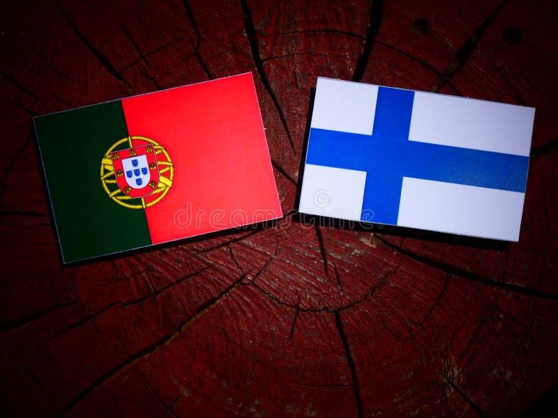 Bandeira portuguesa com bandeira finlandesa em um coto de árvore isolado foto de stock royalty free