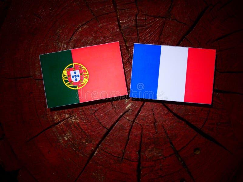 Bandeira portuguesa com bandeira francesa em um coto de árvore isolado fotos de stock royalty free