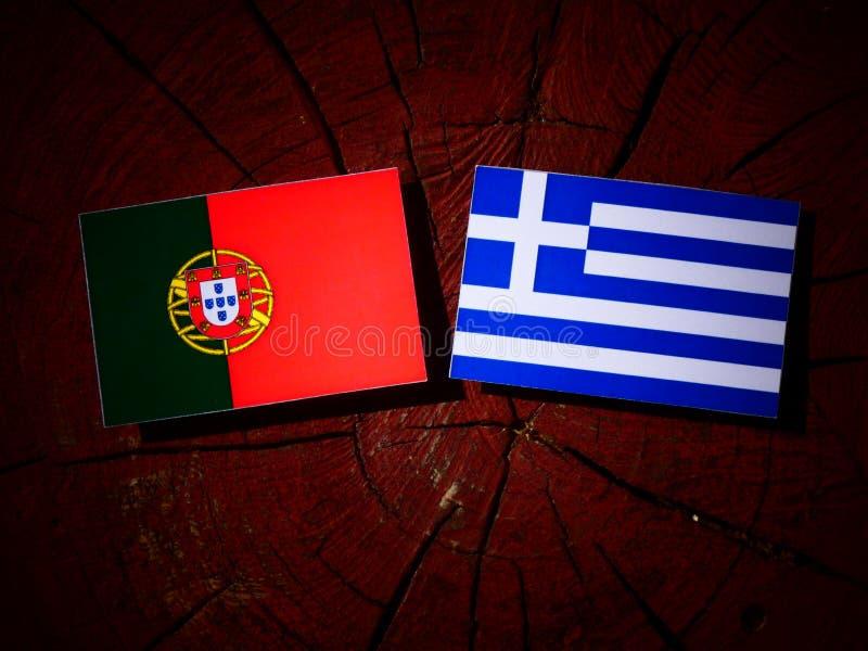 Bandeira portuguesa com bandeira grega em um coto de árvore isolado imagem de stock