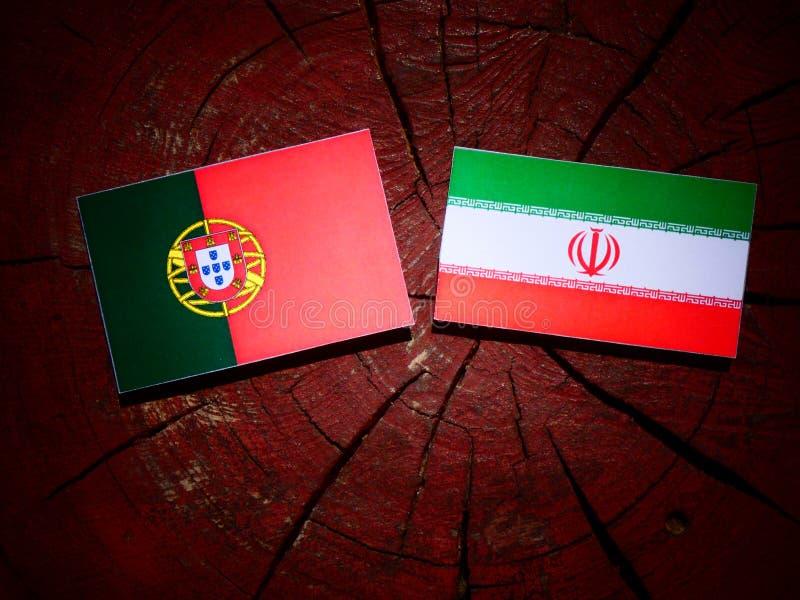 Bandeira portuguesa com bandeira iraniana em um coto de árvore isolado foto de stock