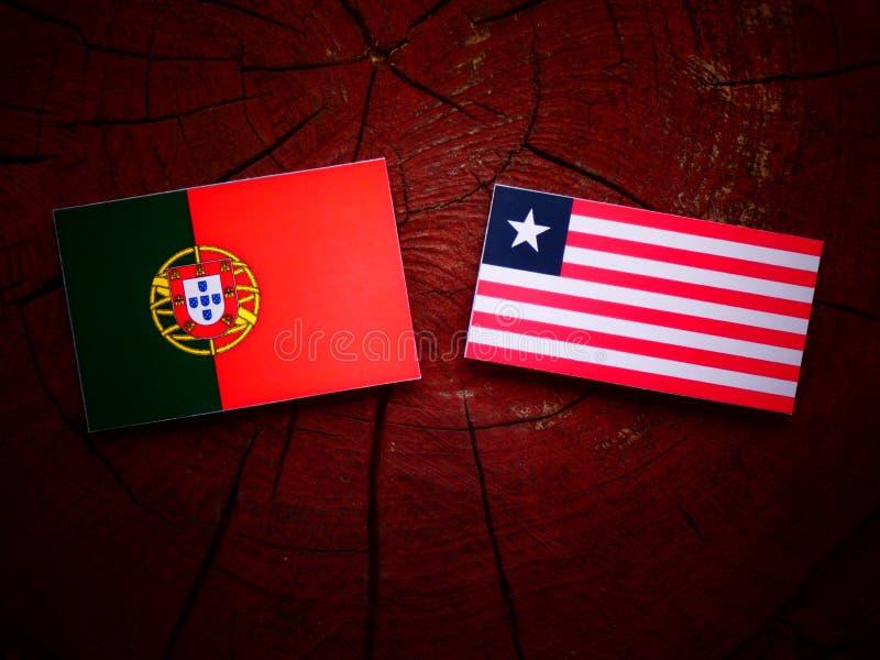 Bandeira portuguesa com bandeira liberiana em um coto de árvore isolado fotos de stock