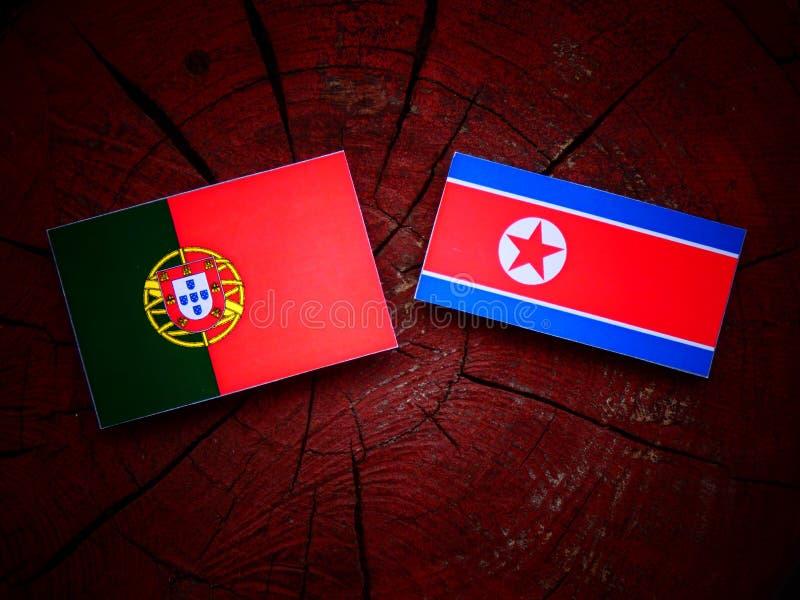 Bandeira portuguesa com bandeira norte-coreana em um coto de árvore imagens de stock royalty free