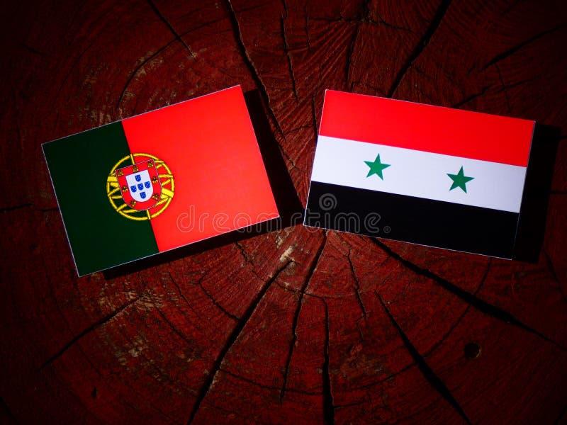 Bandeira portuguesa com bandeira síria em um coto de árvore foto de stock
