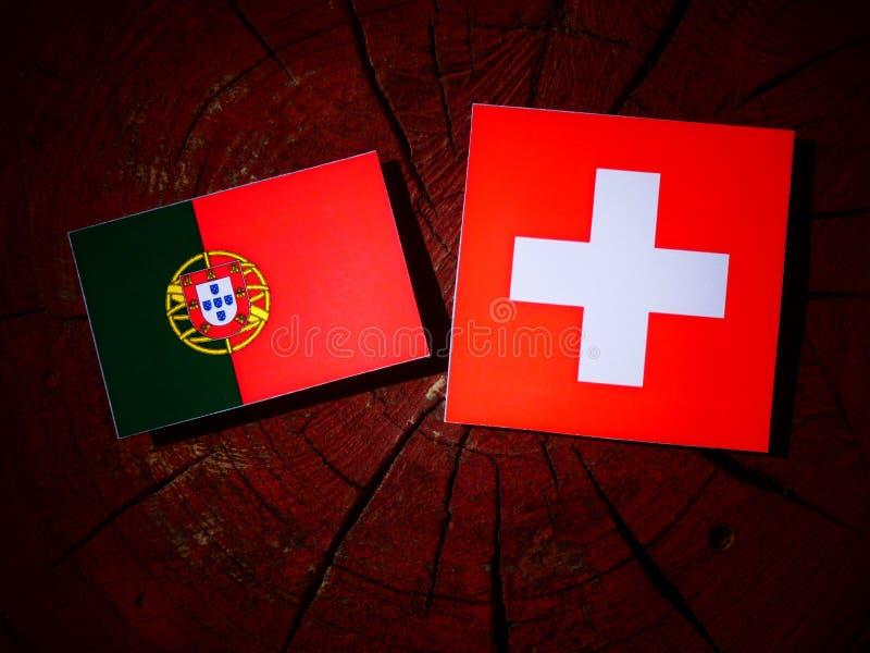 Bandeira portuguesa com bandeira suíça em um coto de árvore foto de stock royalty free