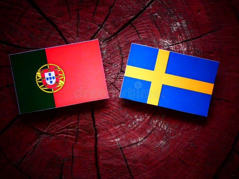 Bandeira portuguesa com bandeira sueco em um coto de árvore fotografia de stock royalty free
