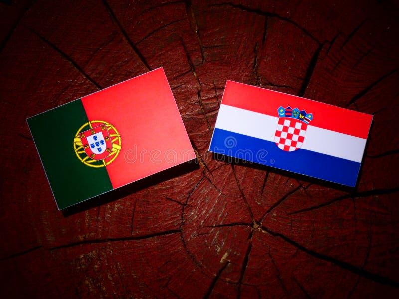 Bandeira portuguesa com bandeira croata em um coto de árvore isolado foto de stock