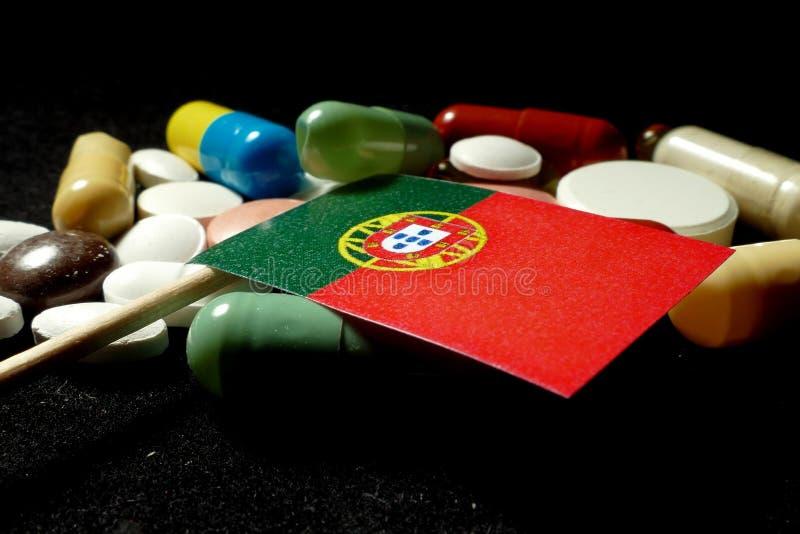 Bandeira portuguesa com lote dos comprimidos médicos isolados na parte traseira do preto imagens de stock