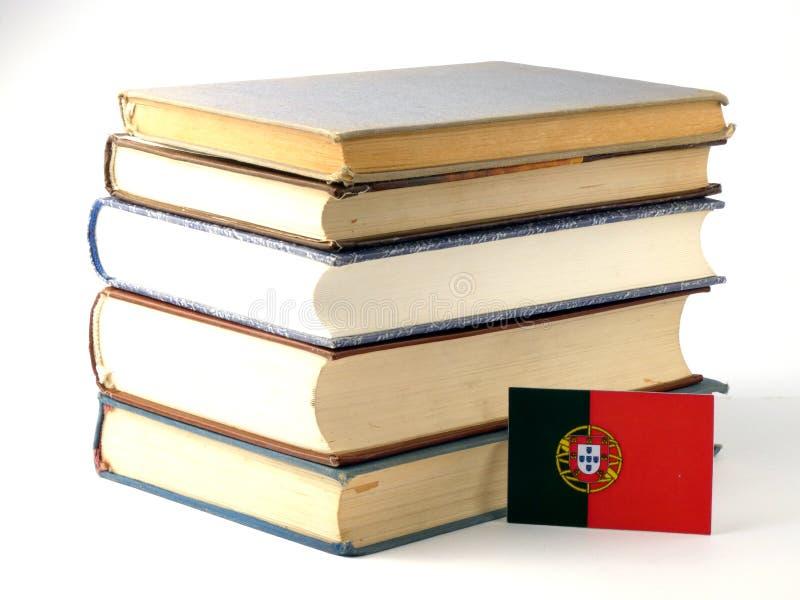 Bandeira portuguesa com a pilha dos livros no fundo branco fotos de stock