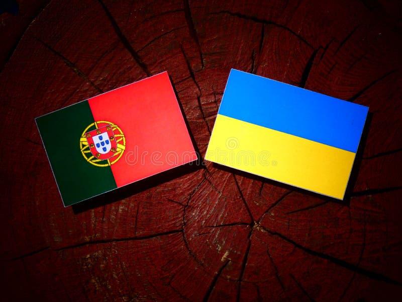 Bandeira portuguesa com bandeira ucraniana em um coto de árvore isolado foto de stock royalty free