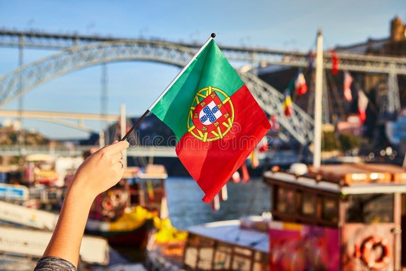 Bandeira portuguesa como um símbolo de Portugal no fundo da ponte Ponte de Dom Luis I na terraplenagem perto do rio Doure dentro imagens de stock