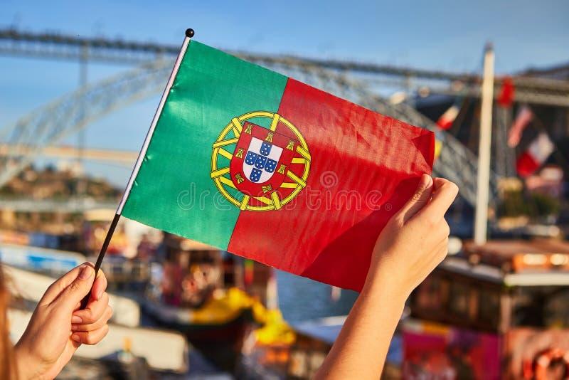 Bandeira portuguesa como um símbolo de Portugal no fundo da ponte Ponte de Dom Luis I na terraplenagem perto do rio Doure dentro foto de stock royalty free