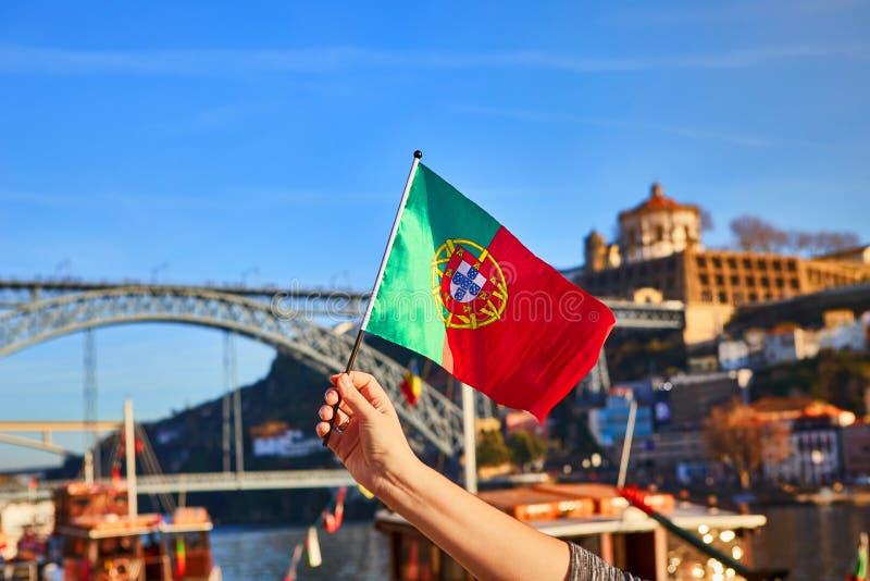 Bandeira portuguesa como um símbolo de Portugal no fundo da ponte Ponte de Dom Luis I na terraplenagem perto do rio Doure dentro fotos de stock