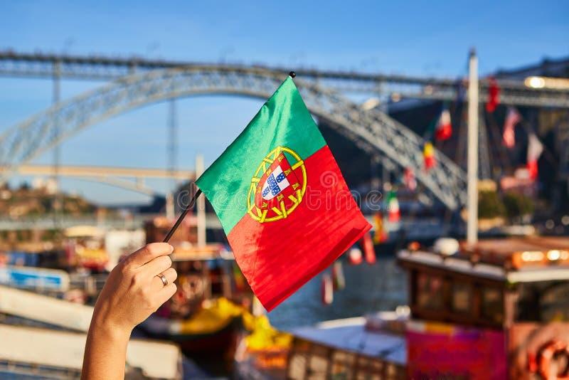 Bandeira portuguesa como um s?mbolo de Portugal no fundo da ponte Ponte de Dom Luis I na terraplenagem perto do rio Doure dentro foto de stock