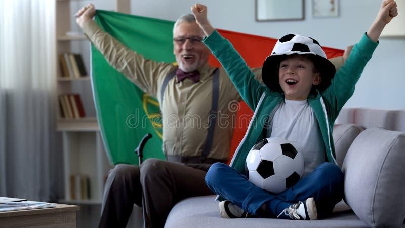 Bandeira portuguesa da terra arrendada do avô, comemorando a vitória da equipe de futebol com menino imagens de stock