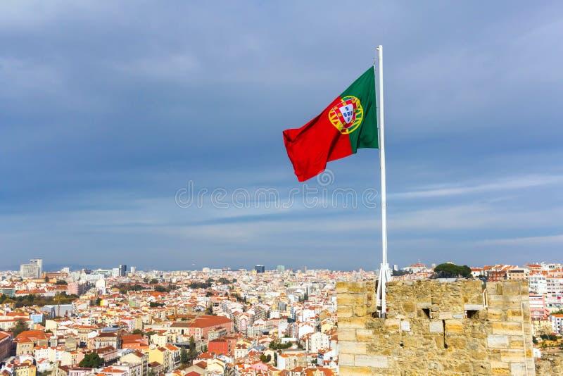 Bandeira portuguesa de ondulação sobre Saint Jorge Castle em Lisboa foto de stock royalty free