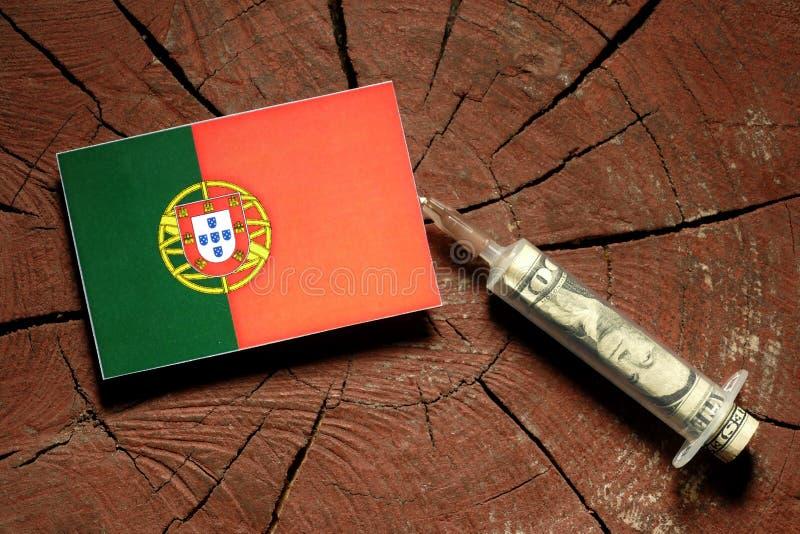 Bandeira portuguesa em um coto com a seringa que injeta o dinheiro imagens de stock