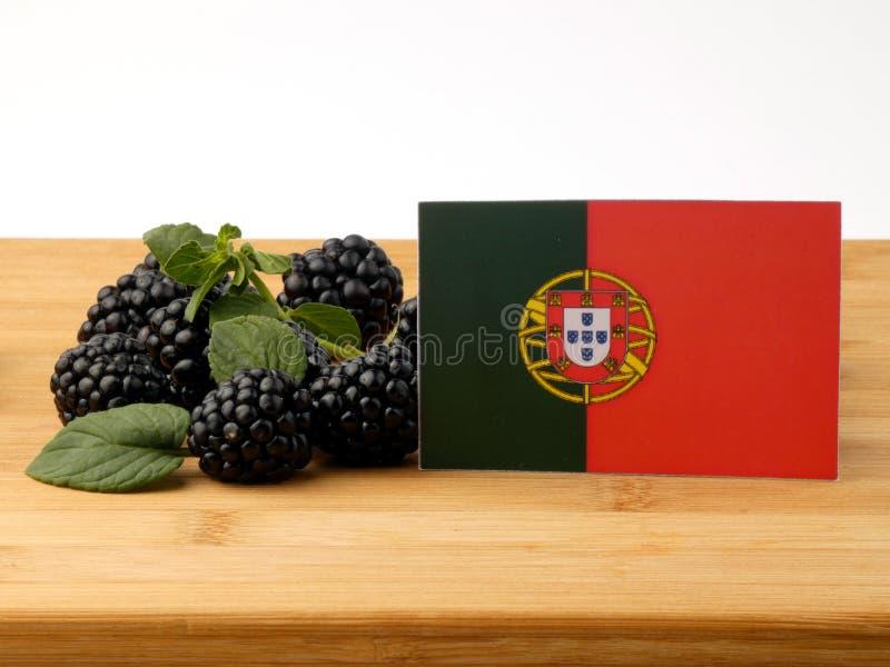 Bandeira portuguesa em um painel de madeira com as amoras-pretas isoladas sobre imagens de stock