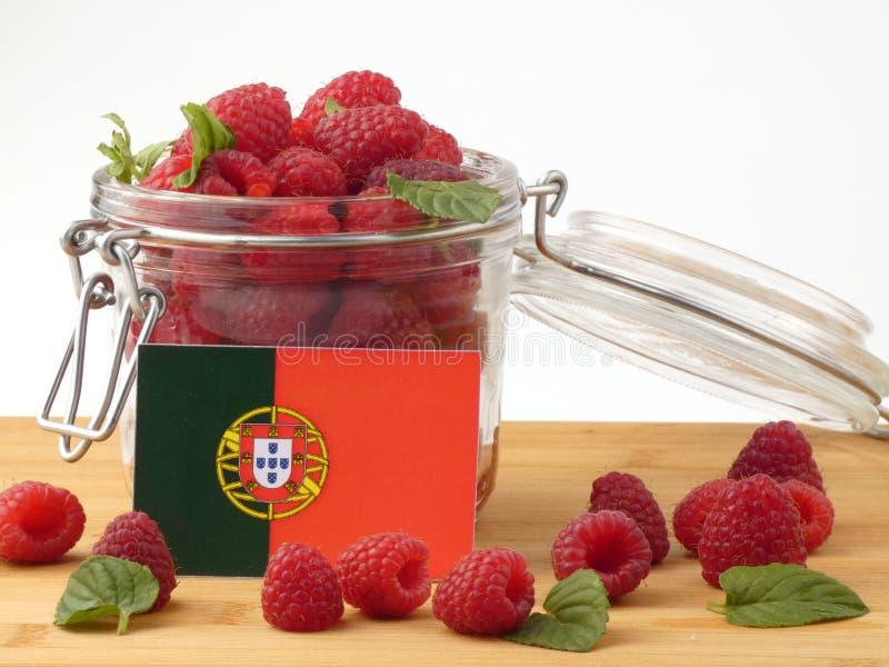 Bandeira portuguesa em um painel de madeira com as framboesas isoladas na fotos de stock