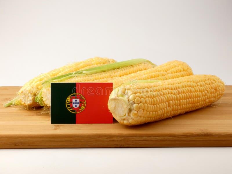 Bandeira portuguesa em um painel de madeira com o milho isolado em um branco imagem de stock