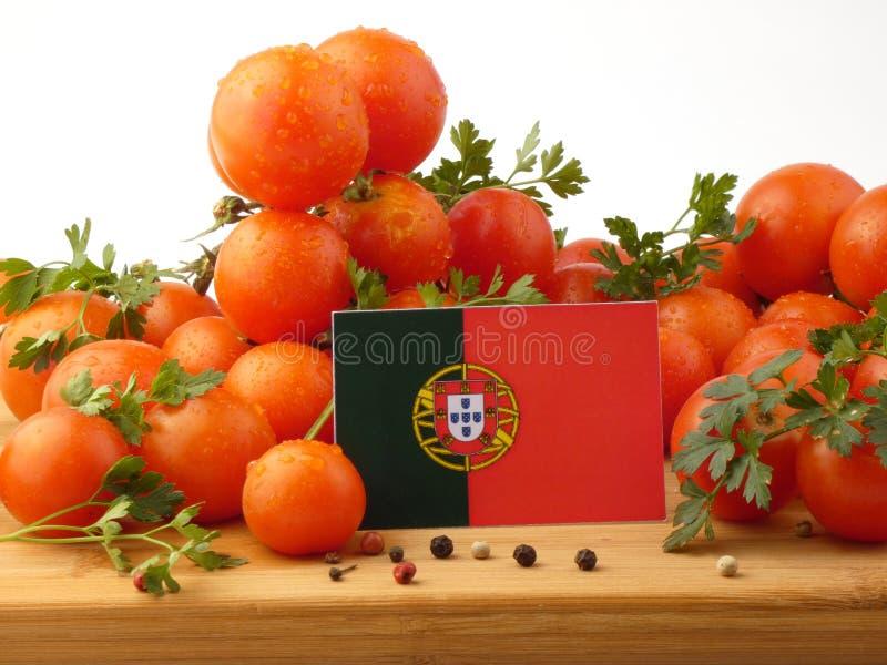 Bandeira portuguesa em um painel de madeira com os tomates isolados em um wh imagem de stock