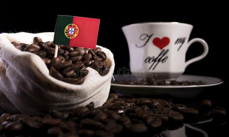 Bandeira portuguesa em um saco com os feijões de café no preto foto de stock royalty free