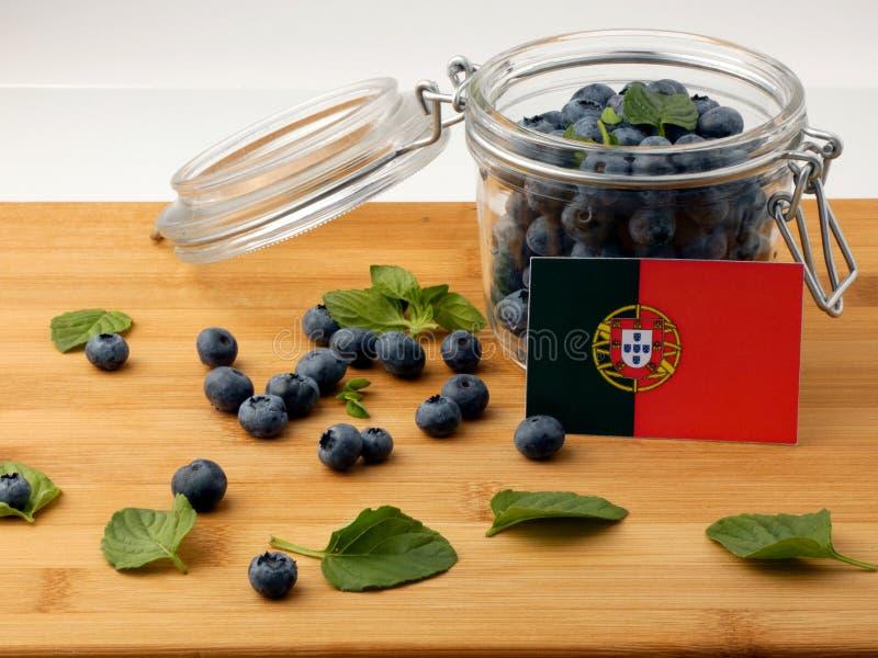 Bandeira portuguesa em uma prancha de madeira com os mirtilos em w imagens de stock royalty free