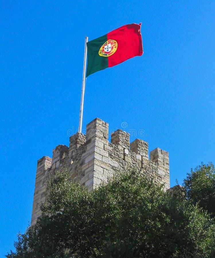 Bandeira portuguesa em uma torre do castelo do ` s de St George em Lisboa imagem de stock royalty free