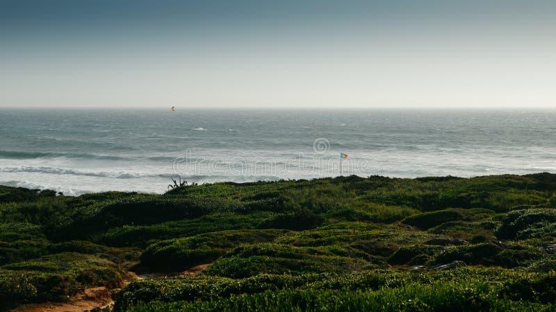 Bandeira portuguesa na praia de Guincho em Cascais, Portugal, um ponto kitesurfing popular fotos de stock royalty free