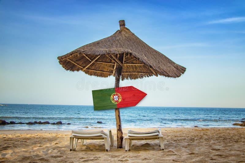 Bandeira portuguesa no sinal de madeira da seta Há dois vadios do sol e um guarda-chuva de sol na praia É um paraíso tropical com fotografia de stock