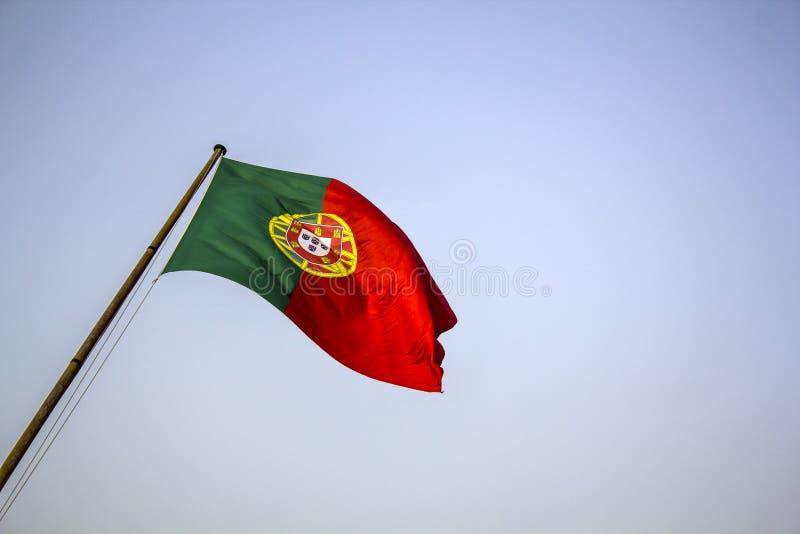 Bandeira portuguesa que acena contra o céu azul fotografia de stock