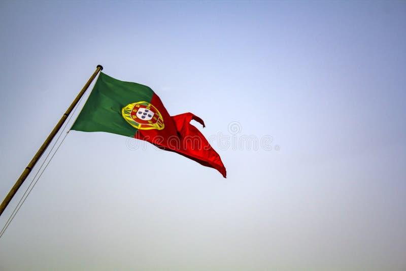 Bandeira portuguesa que acena contra o céu azul imagens de stock