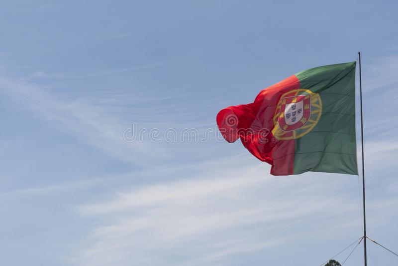 Bandeira portuguesa que acena na frente do céu azul fotos de stock