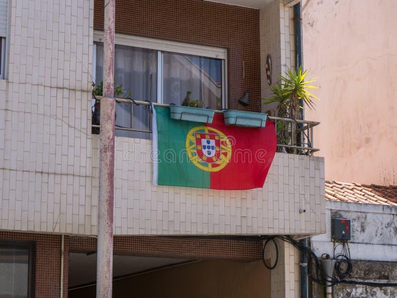 Bandeira portuguesa que haning de um balcão região em Vila do Conde, Porto, Portugal imagem de stock royalty free