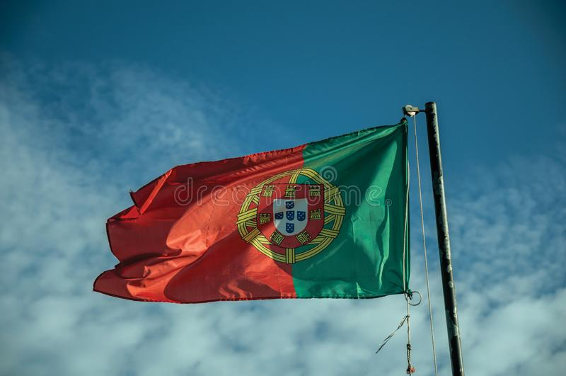 Bandeira portuguesa que vibra no céu azul fotografia de stock