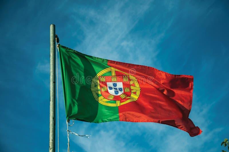 Bandeira portuguesa que vibra no c?u azul imagem de stock royalty free