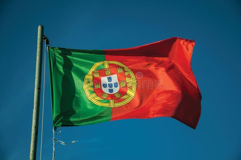 Bandeira portuguesa que vibra no c?u azul fotos de stock royalty free
