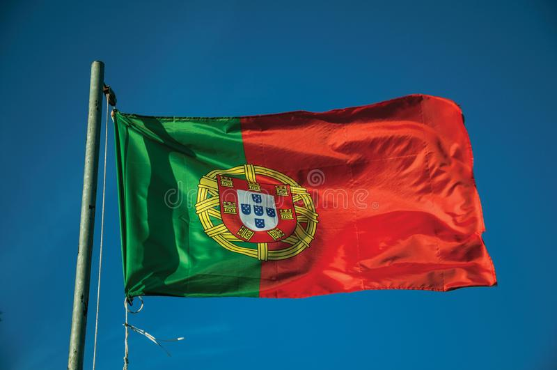 Bandeira portuguesa que vibra no c?u azul imagens de stock royalty free