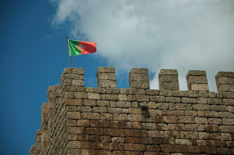 Bandeira portuguesa que vibra sobre a torre do castelo imagens de stock