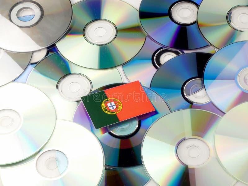 Bandeira portuguesa sobre a pilha do CD e do DVD isolada no branco foto de stock