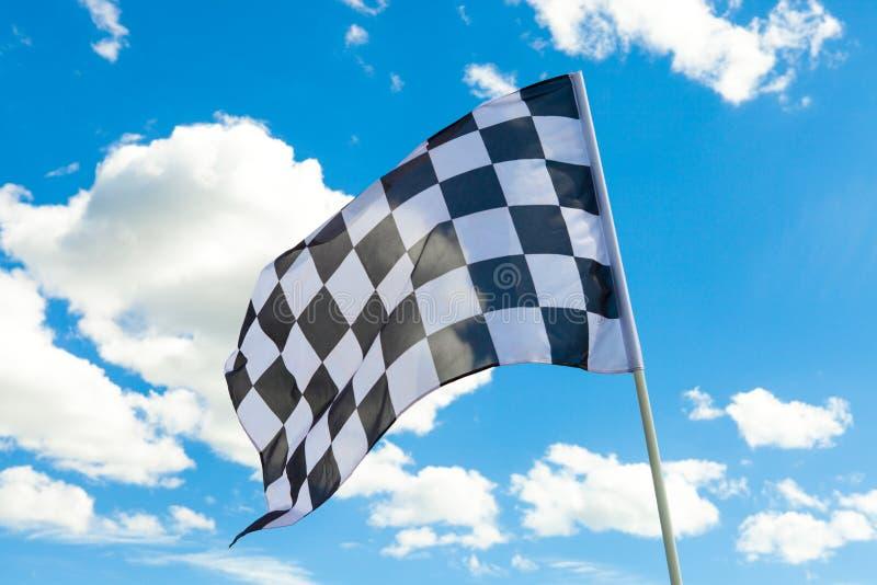 Bandeira quadriculado no mastro de bandeira com as nuvens brancas no fundo imagem de stock