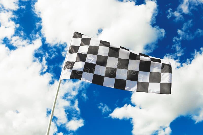 Bandeira quadriculado que acena no vento com as nuvens no fundo - dispare fora Imagem filtrada: efeito processado cruz do vintage imagem de stock