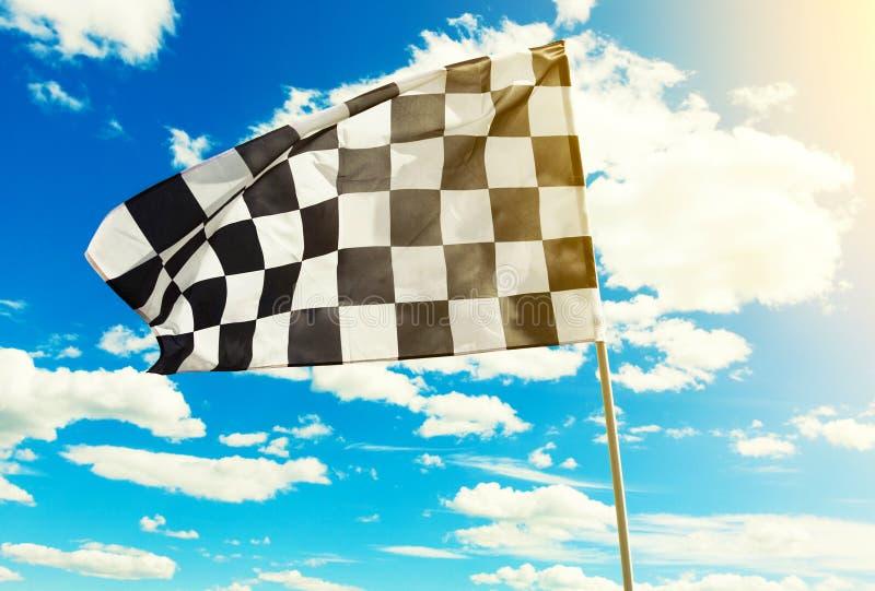 Bandeira quadriculado que acena no vento com o alargamento do sol visível imagem de stock royalty free