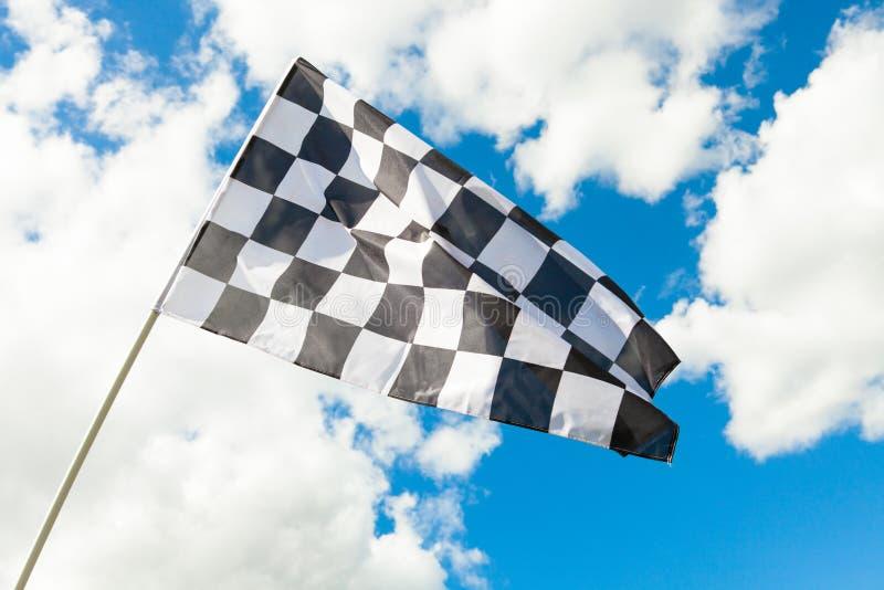 Bandeira quadriculado que acena no vento - nuvens no fundo fotografia de stock
